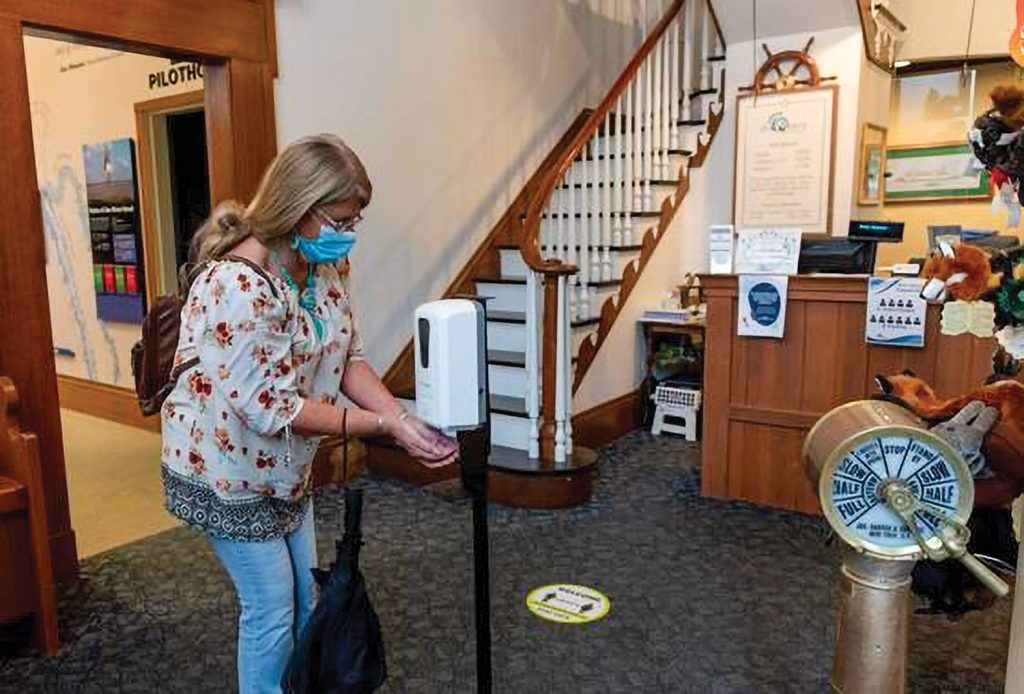 A masked visitor uses a touchless hand sanitizer station at the River Discovery Center in Paducah, Ky. (Photo courtesy of River Discovery Museum)