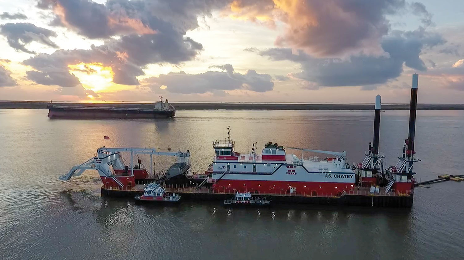 A ship passes the Weeks Marine cutterhead dredge J.S. Chatry as it works in Southwest Pass near the mouth of the Mississippi River. (Photo courtesy of Big River Coalition/P.J. Hahn)