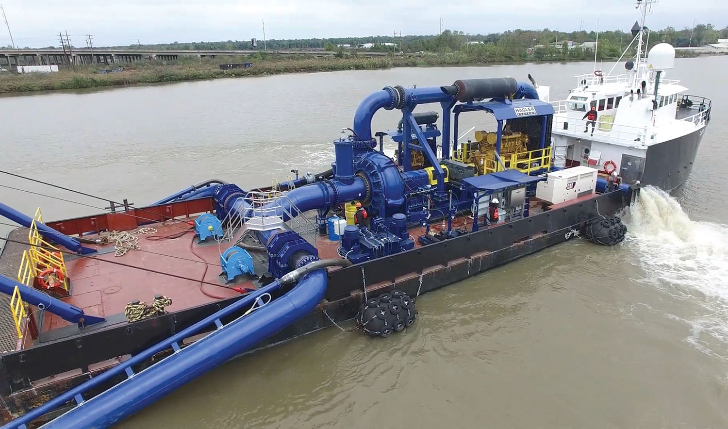 The vessel Captain John Graham tows the dredge Arulaq. The blue piping that is visible represents most of the dredge works. The fine silt sprays on the equipment, which means the deckhands are almost always constantly swabbing the dredge. (Photo courtesy of Brice Civil Contractors)