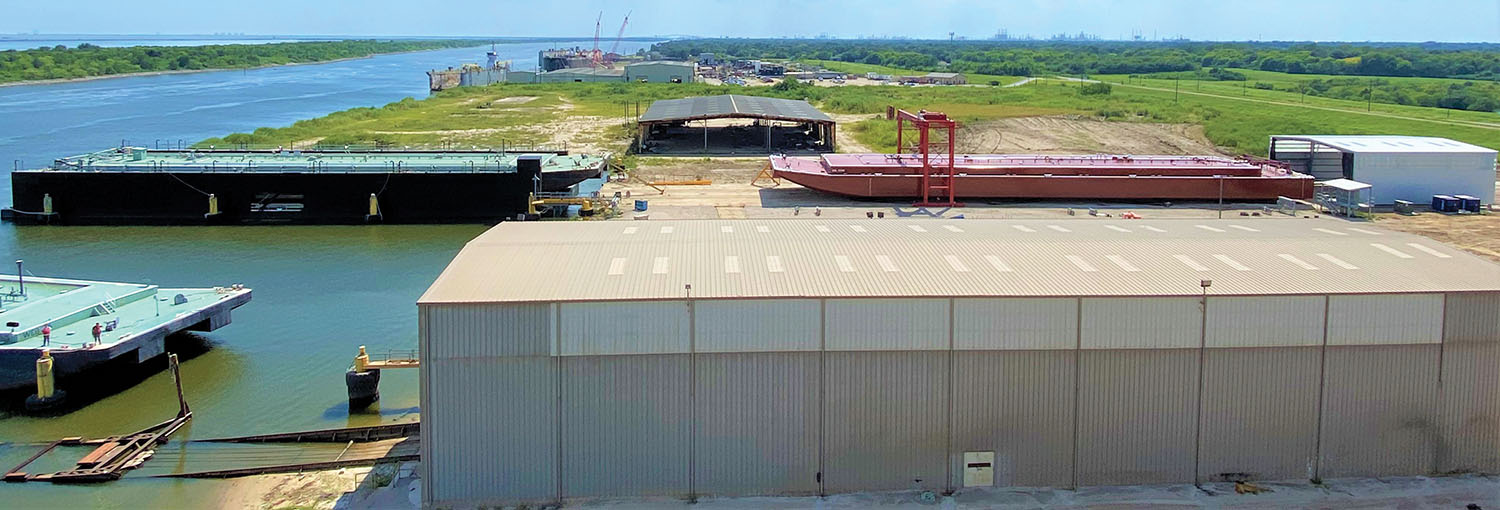 An aerial view of Vessel Repair, with the shipyard's new drydock, rolling gantry crane and paint booth in the background.