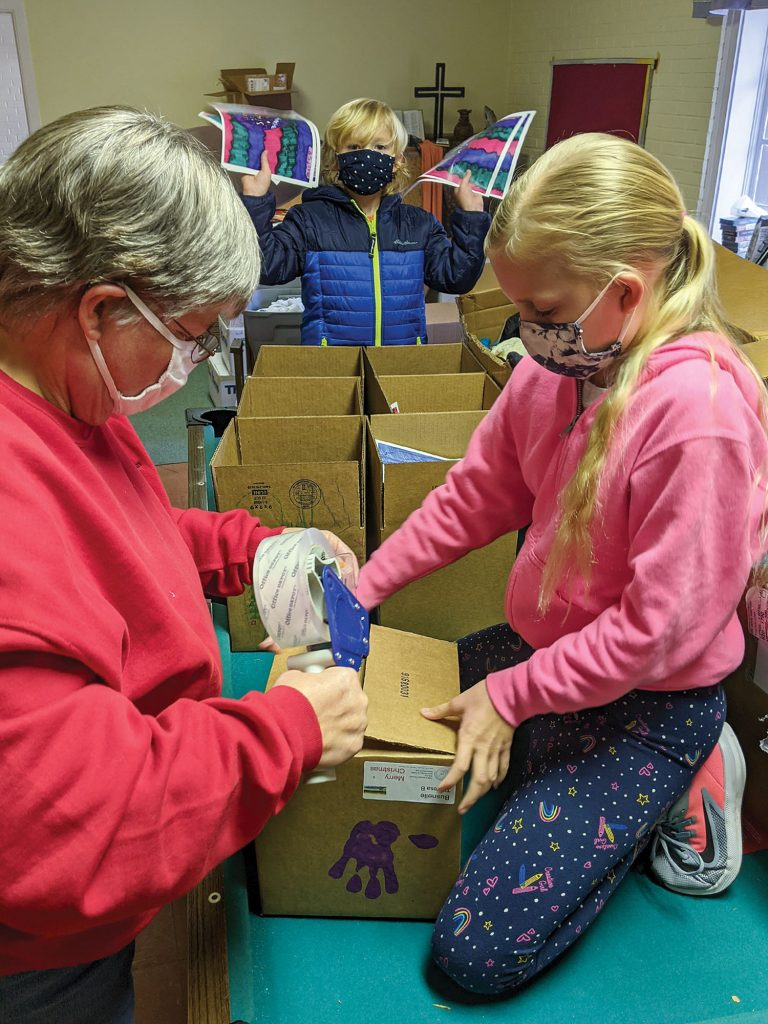 Joy Manthey, longtime towboat captain and chaplain, packs Christmas At Sea gift boxes with Ana and Julian McCormack. Photo by Frank McCormack)
