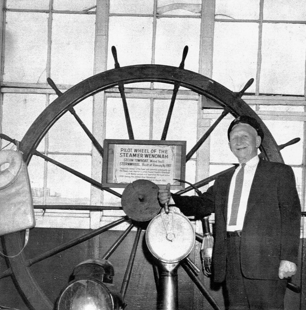 Capt. J.W. Menke with the pilotwheel of the Wenonah aboard the Goldenrod Showboat at St. Louis. (Keith Norrington collection)