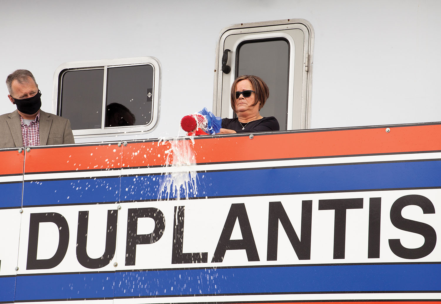 Lisa Duplantis breaks a champagne bottle to christen the boat named for her husband. (Photo by Frank McCormack)