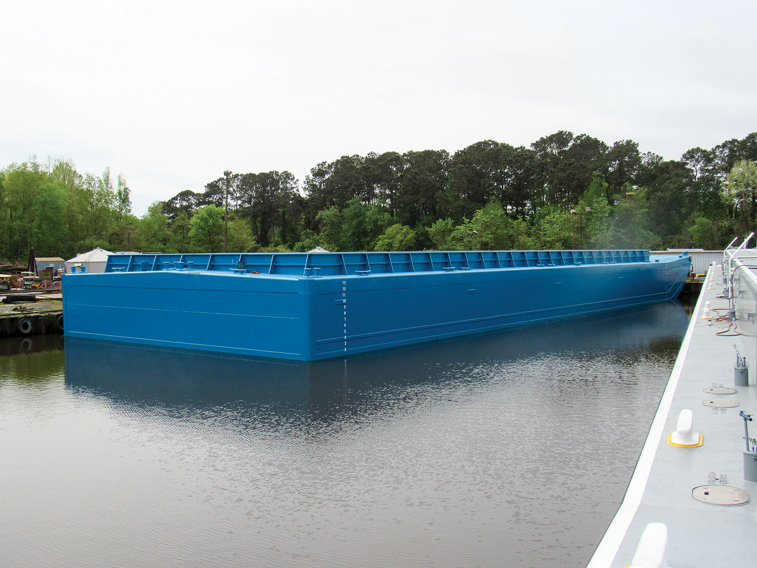 At 200 by 70 feet, the new barge takes up the same space in a tow as two standard hopper barges, but can hold 72 40-foot containers, nearly twice as much as the two standard barges would be able to handle.