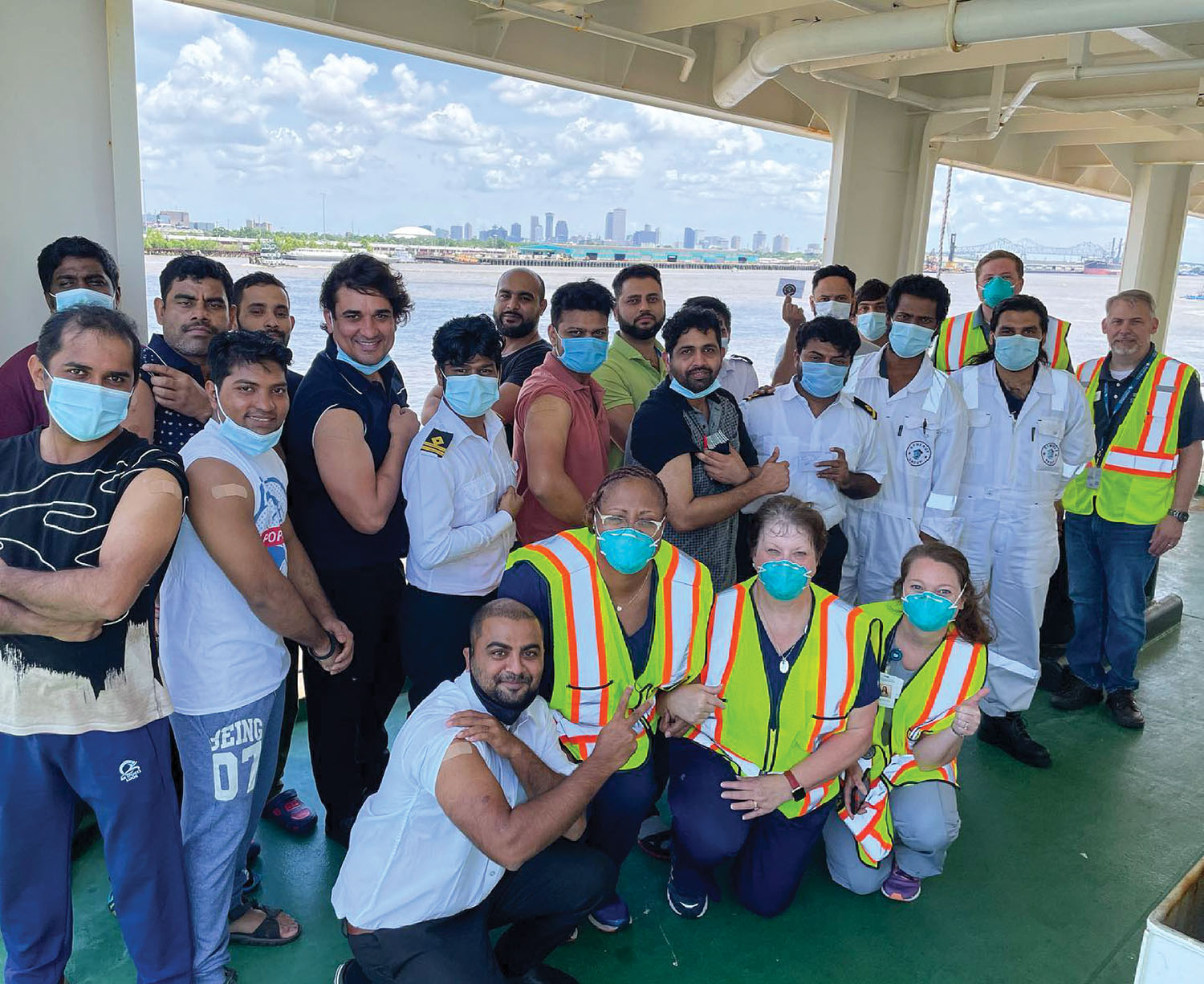 Representatives of Baptist Community Health Services and Global Maritime Ministries, alongside a cargo ship's crew, celebrate a successful mobile health clinic that brought COVID-19 vaccines to seafarers aboard their vessel.