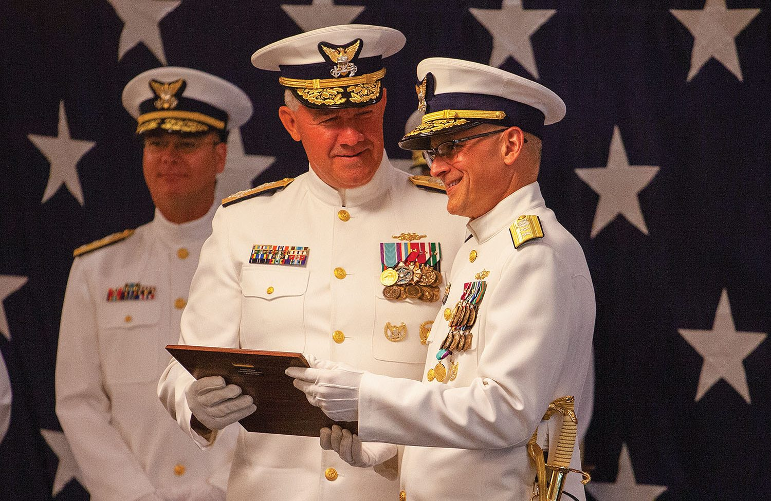 Adm. Karl Schultz (center) congratulates Rear Adm. John Nadeau (right) upon Nadeau's retirement from the Coast Guard June 25. Rear Adm. Richard Timme, who relieved Nadeau as commander of the Eighth Coast Guard District, looks on. (Photo by Frank McCormack)