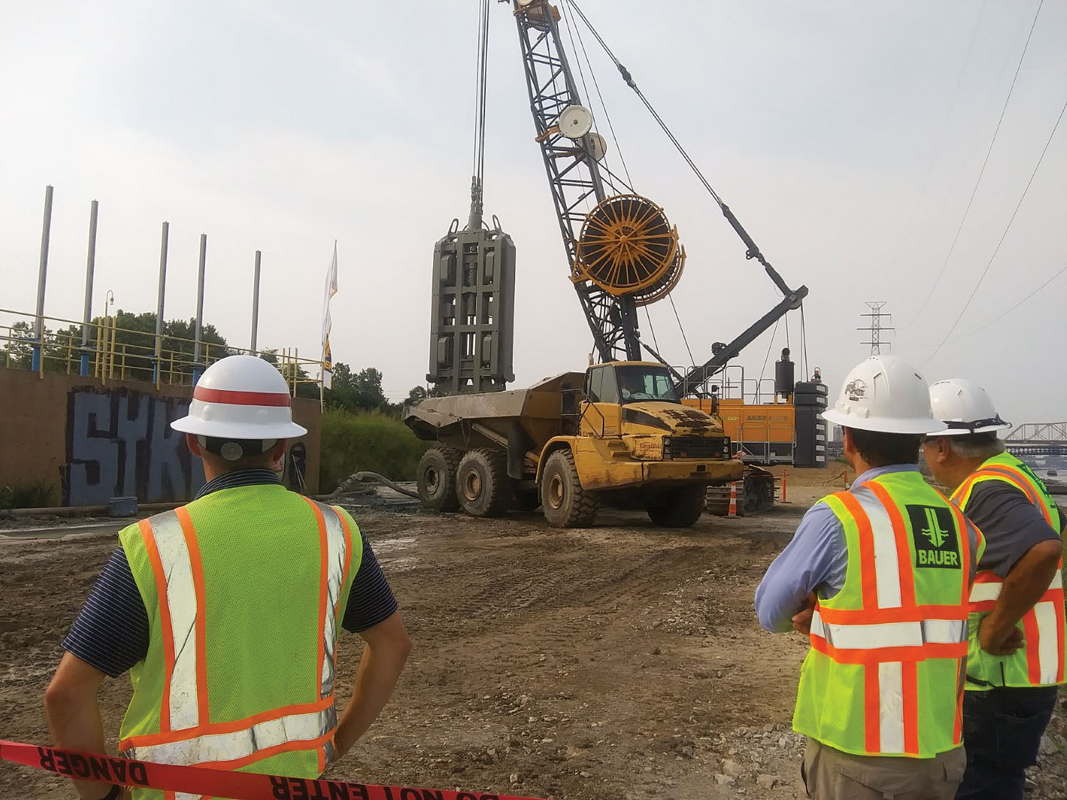 Members of the project team for the East St. Louis seepage wall project look on as a Bauer MC-96 rig in a clamshell configuration removes subsoil on the east bank of the Mississippi River just north of downtown St. Louis. The seepage wall, due to be completed in the fall of 2022, is the largest project of its type and will protect the levee system against under-seepage. (Photo by David Murray)