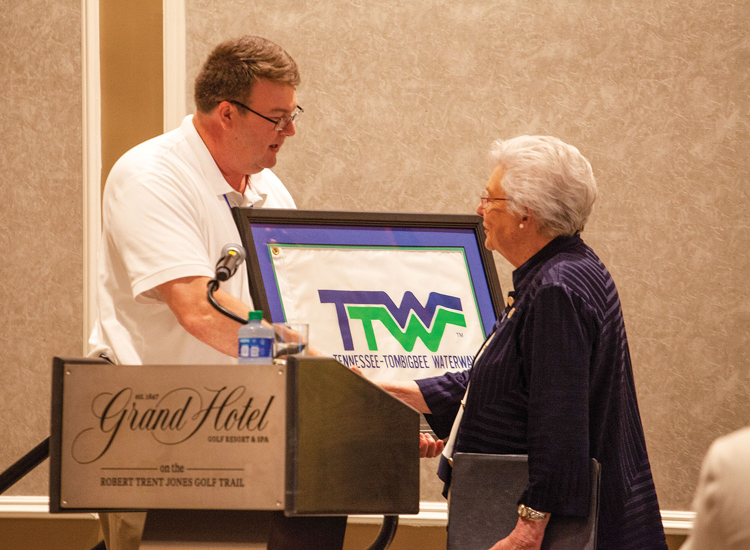 Mitch Mays, administrator of the Tennessee-Tombigbee Waterway Development Authority and president of the Tennessee-Tombigbee Waterway Development Council, presents Alabama Gov. Kay Ivey with a commemorative flag from the waterway's official opening in the 1980s. (Photo by Frank McCormack)