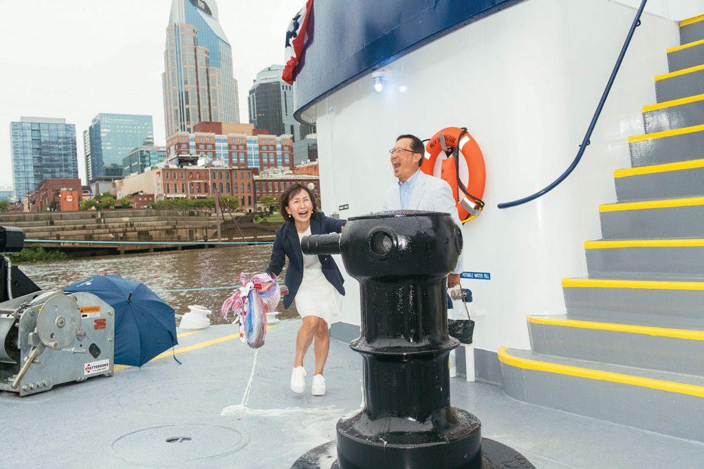 """Namesake Youngsuk """"YS"""" Chi looks on while Sung Chi breaks bottle. (Photo courtesy of Ingram Barge Company)"""