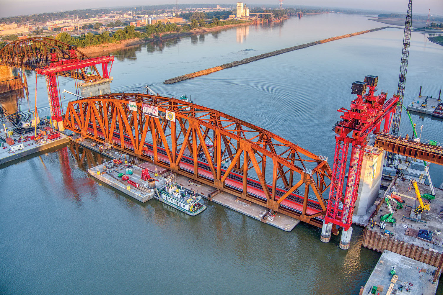 The first of three trusses is slowly raised into position to be placed on the Merchants Bridge on the Mississippi River in downtown St. Louis. (Photo courtesy of Walsh Construction and Trey Cambern Photography)